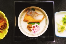 Broiled fish dabbed with soy sauce atop a shiso leaf, accompanied with pickled lotus root and a dollop of miso.